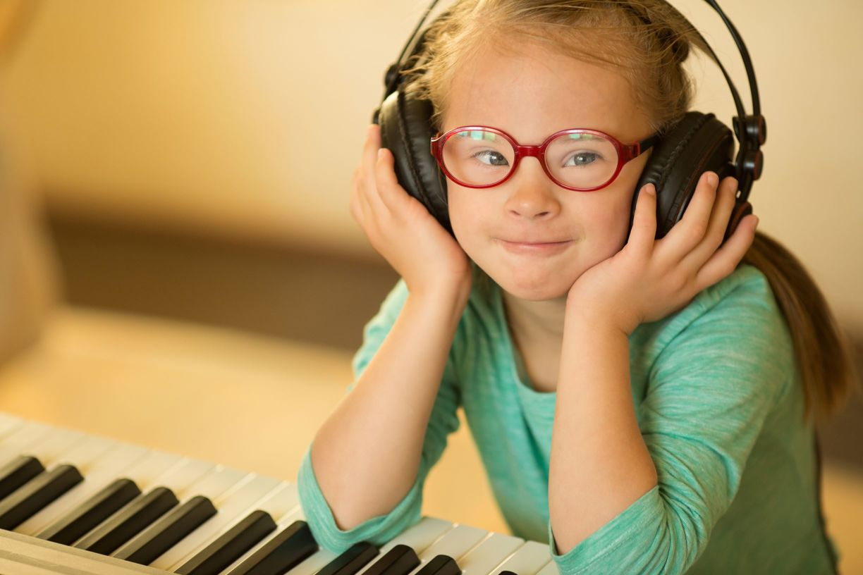 Girl with headphones at keyboard