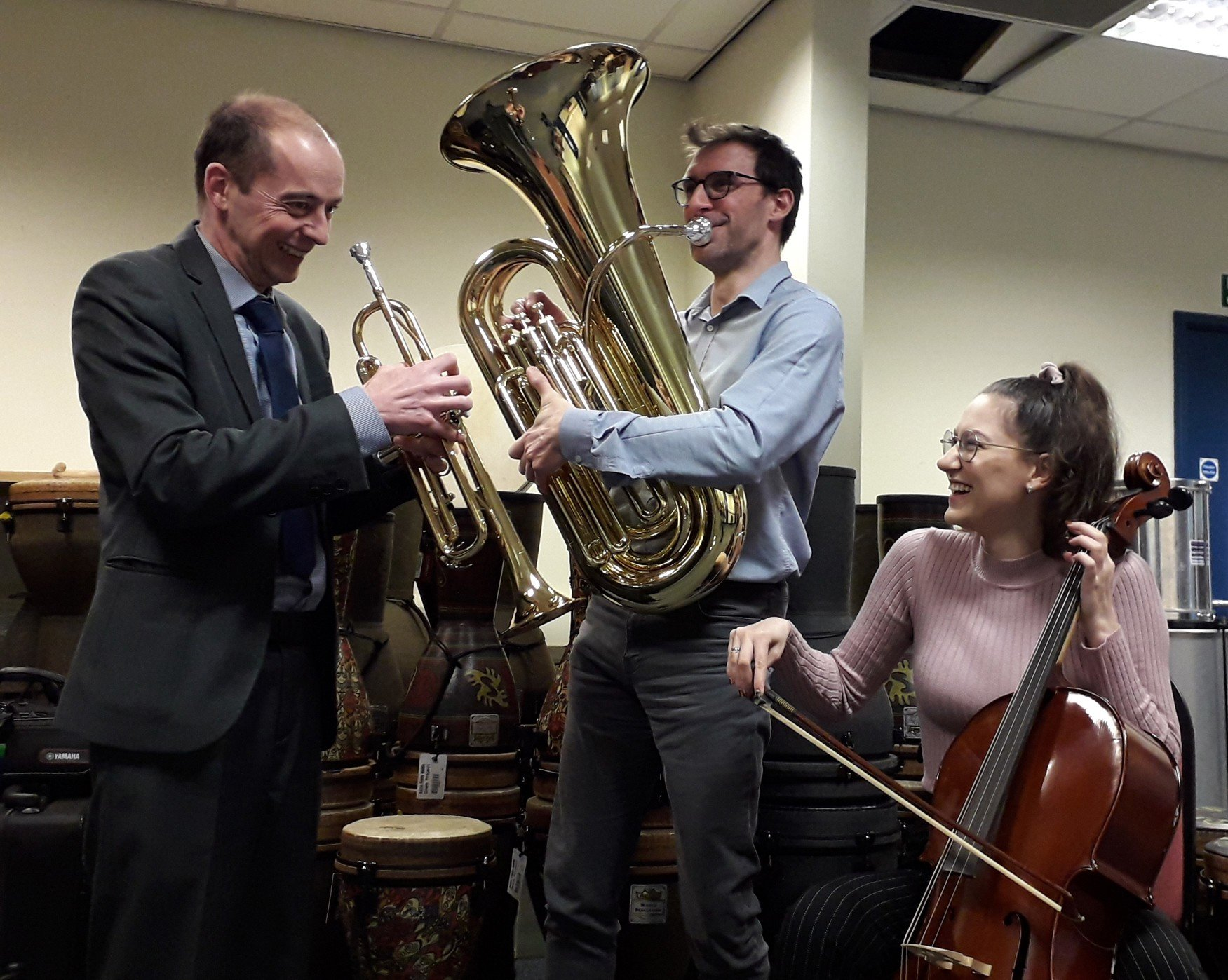 three members of Severn Arts team trying instruments - trumpet, tuba and cello