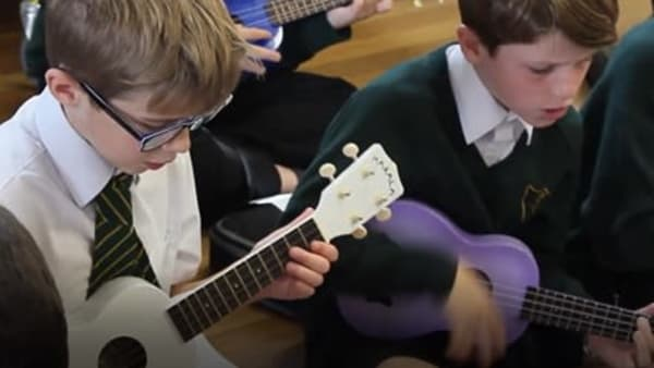 two boys playing ukuleles