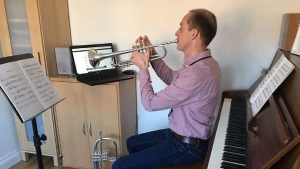 teacher playing trumpet for online lessons