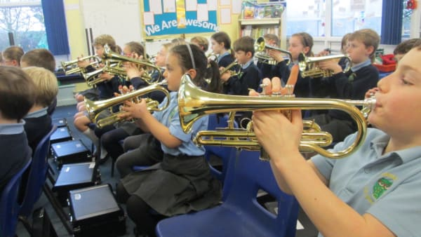 class of school children playing brass instruments