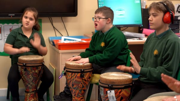 three young people drumming